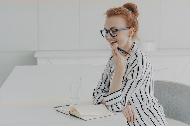 Mulher sorridente segurando um celular e falando com o assistente de reconhecimento de voz digital virtual em casa