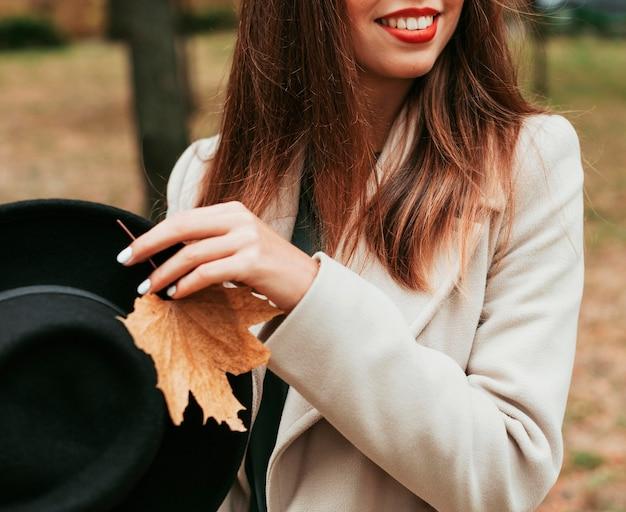 Mulher sorridente segurando um chapéu preto e uma folha