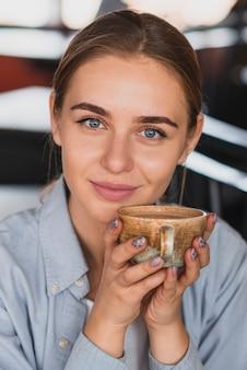 Mulher sorridente segurando um copo perto do rosto