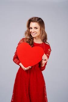 Mulher sorridente segurando um grande coração vermelho