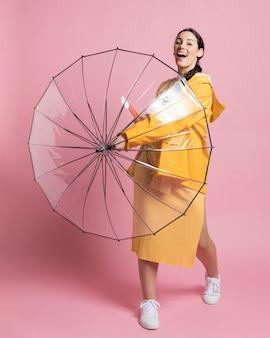Mulher sorridente segurando um guarda-chuva aberto