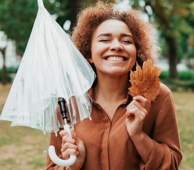Mulher sorridente segurando um guarda-chuva e uma folha