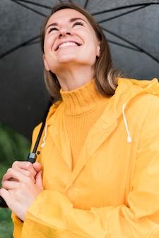 Mulher sorridente segurando um guarda-chuva preto aberto ao ar livre