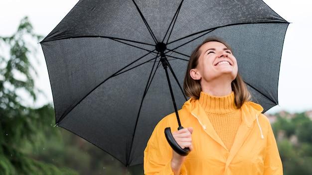 Mulher sorridente segurando um guarda-chuva preto aberto