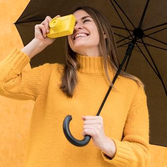 Mulher sorridente segurando um guarda-chuva preto e uma câmera amarela