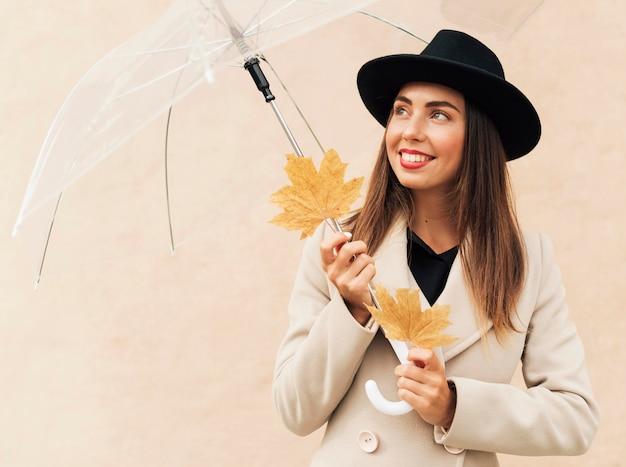 Mulher sorridente segurando um guarda-chuva transparente