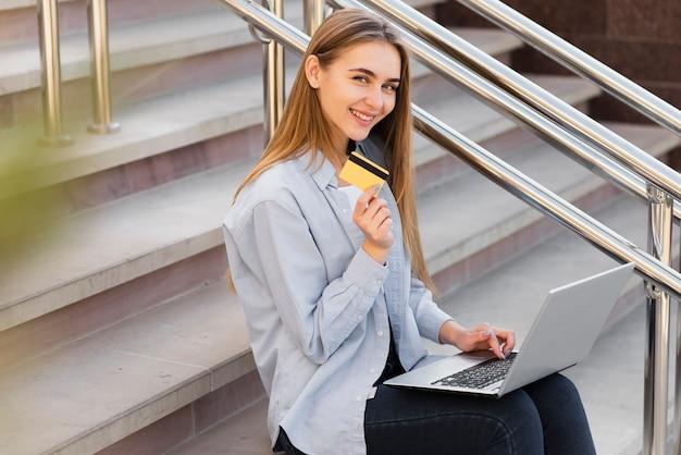 Mulher sorridente segurando um laptop e um cartão de crédito
