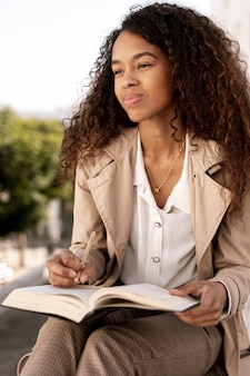 Mulher sorridente segurando um livro aberto ao ar livre