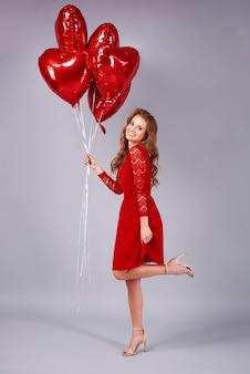 Mulher sorridente segurando um monte de balões em formato de coração