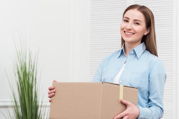 Mulher sorridente segurando um pacote dentro de casa