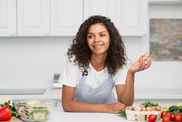 Mulher sorridente segurando um pouco de batata