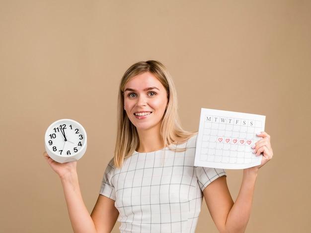 Mulher sorridente segurando um relógio e seu calendário de período