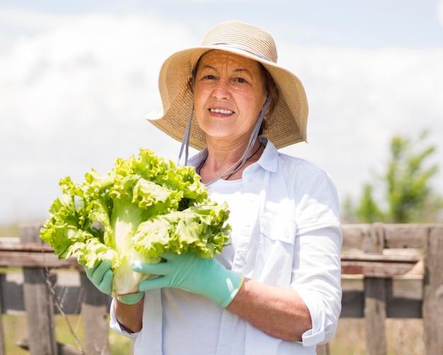 Mulher sorridente segurando um repolho fresco