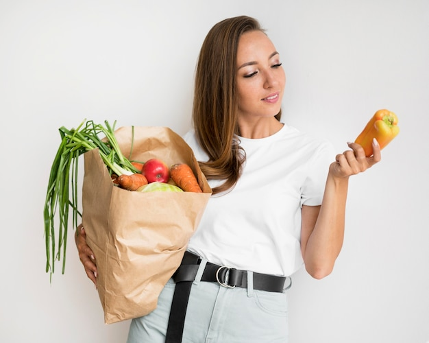 Mulher sorridente segurando um saco de papel com comida