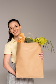 Mulher sorridente segurando um saco de papel com legumes