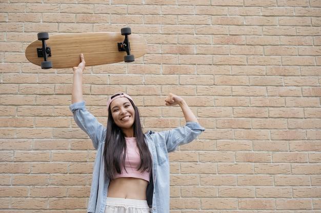 Mulher sorridente segurando um skate no fundo da parede de tijolos