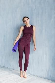 Mulher sorridente segurando um tapete de ioga enquanto descansava