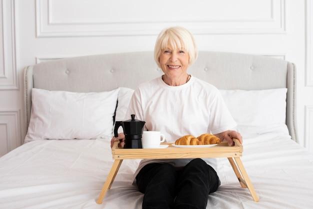 Mulher sorridente segurando uma bandeja no quarto