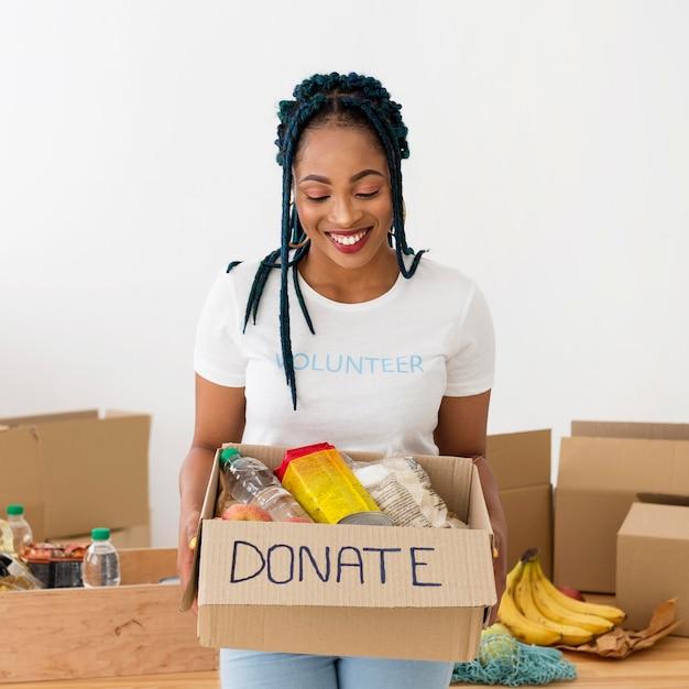 Mulher sorridente segurando uma caixa de doações