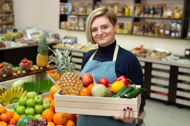 Mulher sorridente segurando uma caixa de madeira com legumes e frutas na loja
