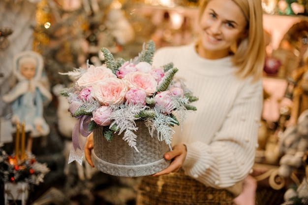 Mulher sorridente segurando uma caixa de padrão de suéter cinza com rosas peônia rosa claro decoradas com galhos de pinheiro.