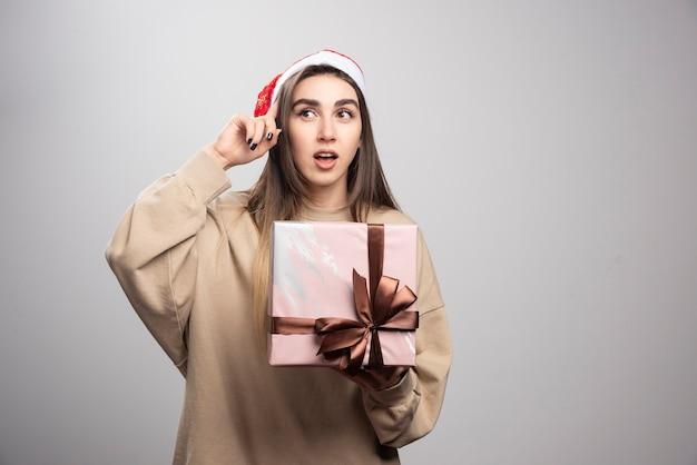 Mulher sorridente segurando uma caixa de presente de natal.