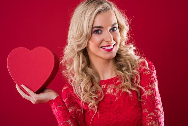 Mulher sorridente segurando uma caixa vermelha em formato de coração