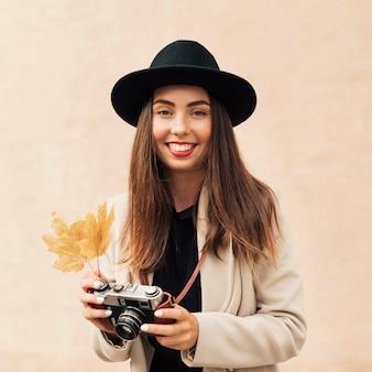 Mulher sorridente segurando uma câmera e uma folha