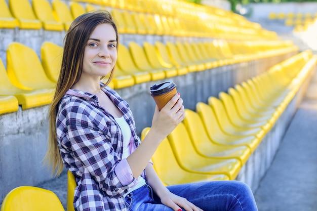 Mulher sorridente segurando uma caneca de papel sentada no estádio