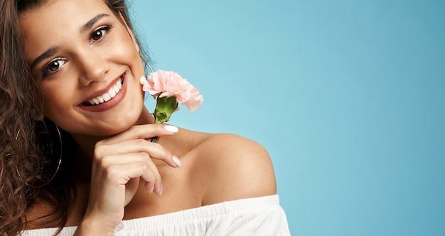 Mulher sorridente segurando uma flor de rosa
