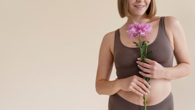 Mulher sorridente segurando uma flor