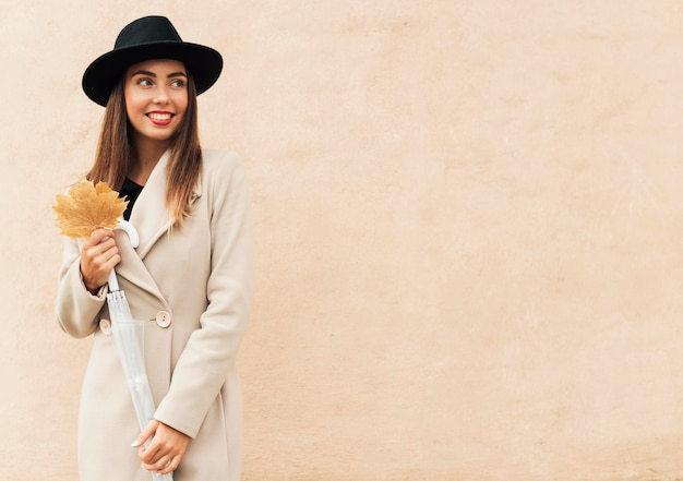 Mulher sorridente segurando uma folha outonal com espaço de cópia
