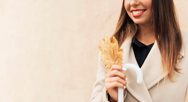 Mulher sorridente segurando uma folha outonal do lado de fora