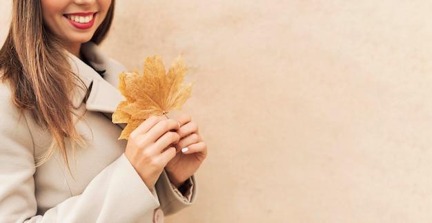 Mulher sorridente segurando uma folha outonal
