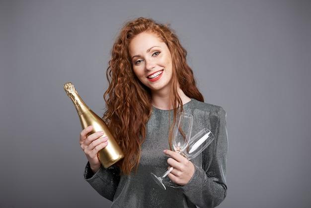 Mulher sorridente segurando uma garrafa de champanhe e uma taça de champanhe