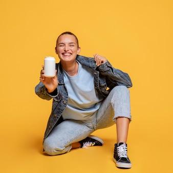 Mulher sorridente segurando uma lata de refrigerante