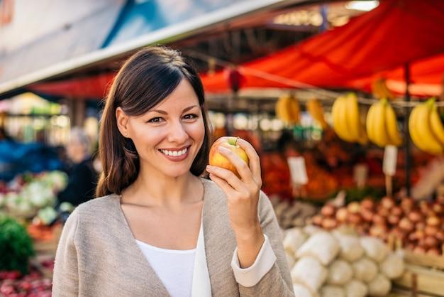 Mulher sorridente segurando uma maçã no mercado dos fazendeiros