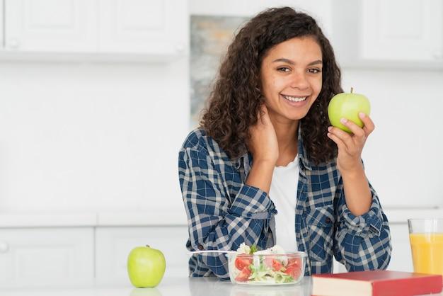Mulher sorridente, segurando uma maçã verde
