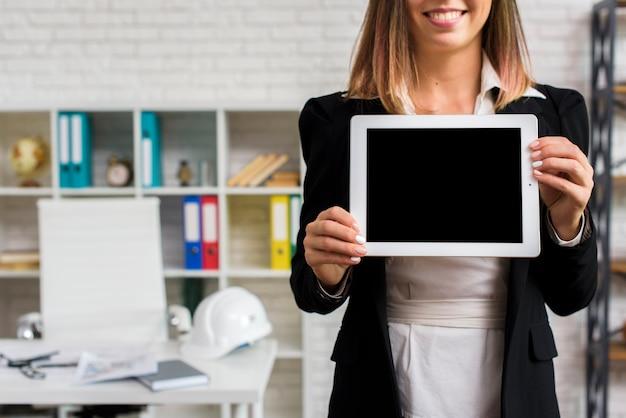 Mulher sorridente segurando uma maquete de tablet