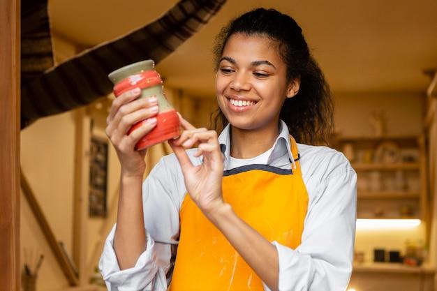 Mulher sorridente segurando uma panela de barro, tiro médio