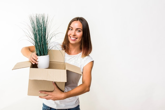 Mulher sorridente segurando uma planta