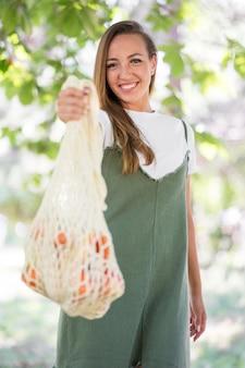 Mulher sorridente segurando uma sacola biodegradável com guloseimas