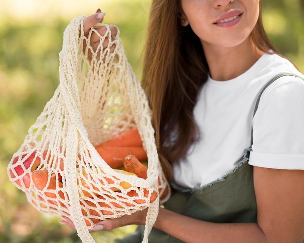 Mulher sorridente segurando uma sacola com lanches saudáveis