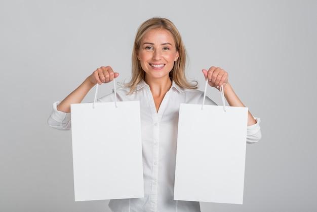 Mulher sorridente segurando uma sacola de compras em cada mão