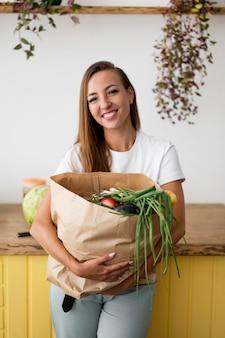 Mulher sorridente segurando uma sacola de compras