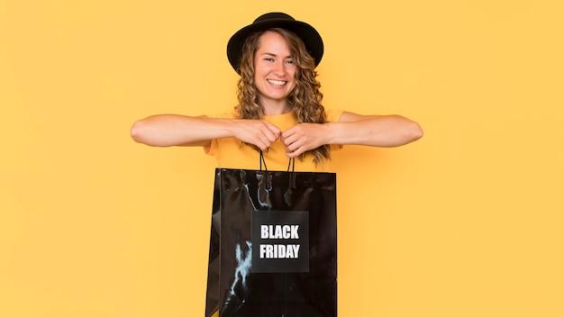 Mulher sorridente segurando uma sacola preta de compras sexta-feira