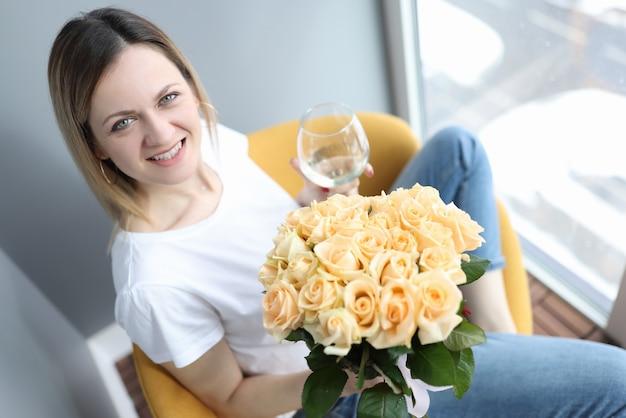 Mulher sorridente segurando uma taça de vinho e um buquê de flores nas mãos