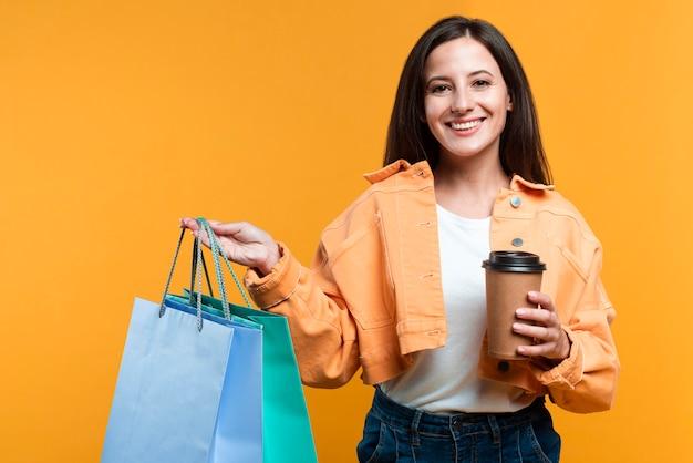 Mulher sorridente segurando uma xícara de café e sacolas de compras