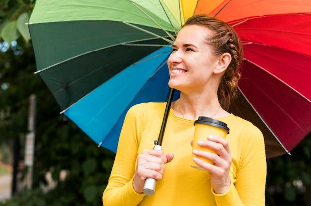 Mulher sorridente segurando uma xícara de café sob um guarda-chuva colorido