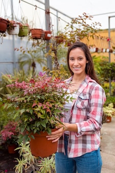Mulher sorridente segurando vaso de flores grande